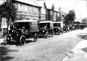 a line of vans with the Whitehead company logo c1916