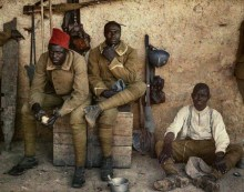 Three Senegalese soldiers in uniform, including red caps, resting between fighting.
