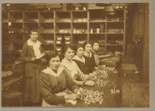 Five women sit at a workbench in front of piles of metal pieces. Another woman stands behind them
