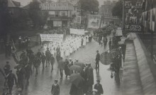 Spectators with umbrellas line the road as groups of soldeirs and nurses carrying banners walk past