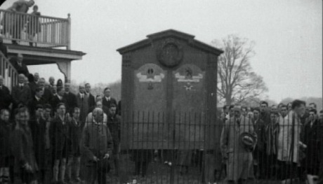 A crowd of people stand around a wooden memorial board decorated with a wreath